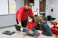 Mr. McElroy helps students as they work to program their new robots